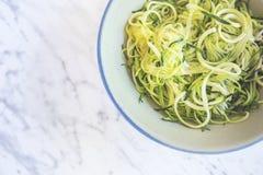 Zucchinispagetti eller nudlar & x28; zoodles& x29; i en bunke med marmorlodisar royaltyfri bild