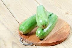 Zucchinizucchini på skärbräda på trätabellen Arkivfoton