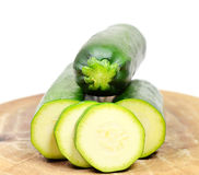 Zuchini. Cut zuchini on wooden board on white Stock Photography