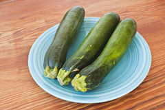 Zuchini on a turquoise plate and a table. Royalty Free Stock Photos