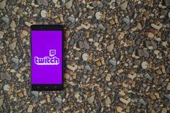 Zucken Sie Logo auf Smartphone auf Hintergrund von kleinen Steinen Stockfotografie