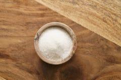 Zucker in der hölzernen Schüssel auf Holztisch von oben Lizenzfreie Stockfotografie