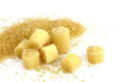 Zucker und Zuckerrohr, Stück des Zuckerrohrs geschnitten und granulierter Zucker des Zuckerrohrs lokalisiert auf weißem Hintergru stockfotografie