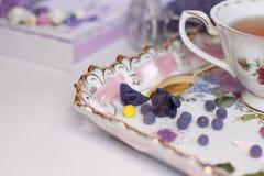 Zucker von den Blumen eines Veilchens mit einer Tasse Tee Lizenzfreie Stockfotos