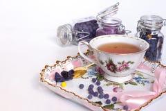 Zucker von den Blumen eines Veilchens mit einer Tasse Tee Stockbilder