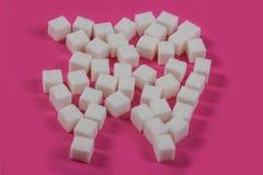 Zucker zerst?rt das Zahnemaille und f?hrt zu Zahnverfall Zuckerwürfel werden in Form eines Zahnes und eines Loches ausgebreitet stockfotos