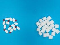 Zuckerersatzpillen und -Raffinade auf Blau stockfotos