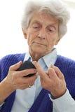 Zuckerkranke alte Frau, die ihr Zuckergehalt misst Lizenzfreie Stockfotos