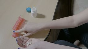 Zuckerkranke junge Mutter, die ihre Pillen für die nächste Woche unter Verwendung eines Organisatorkastenplaners vorbereitet - stock footage