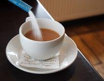 Zuckern Sie das Fließen in ein Cup Lizenzfreie Stockfotografie