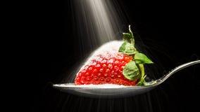Zuckern Sie das Gießen über eine Erdbeere auf einem Löffel Stockfotografie
