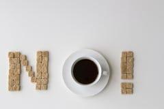 Zuckern Sie die Würfel und Tasse Kaffee, die als Wort NEIN auf weißem Hintergrund vereinbart werden Unhealty süßes Suchtkonzept d Stockfoto