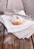 Zuckern Sie pulverisierte Zimtdonuts auf Backpapier auf weißem hölzernem Hintergrund Stockfoto