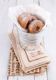 Zuckern Sie pulverisierte Zimtdonuts in einem Blecheimer auf weißem hölzernem Hintergrund Lizenzfreies Stockfoto
