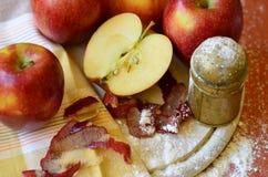 Zuckern Sie Schüttel-Apparat, Äpfel und Schalenmesser auf hölzernem hackendem Brett Stockfotos