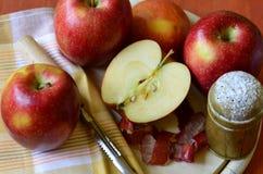 Zuckern Sie Schüttel-Apparat, Äpfel und Schalenmesser auf hölzernem hackendem Brett Lizenzfreie Stockbilder