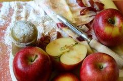 Zuckern Sie Schüttel-Apparat, Äpfel und Schalenmesser auf hölzernem hackendem Brett Lizenzfreie Stockfotos