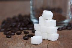 Zuckern Sie Würfel und Kaffeebohnen mit Glasschale Lizenzfreies Stockbild