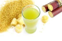 Zuckern Sie Zuckerrohrsaft und neuen Zuckerrohrschnitt, Stock, granulierter Zuckergelbes Braun auf weißem Hintergrund lizenzfreie stockfotos