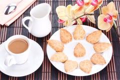 Zuckerplätzchen und ein Tasse Kaffee mit Sahne stockfotos