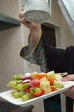 Zuckerpulver, das über Fruchtplatte gießt Stockfotos