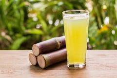 Zuckerrohrsaft mit Stück des Zuckerrohrs auf hölzernem Hintergrund stockfoto