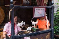 Zuckersüßigkeitskunst gemacht von einer Frau durch eine Frau hinter Stange in der Jinli-Fußgänger-Straße Stockbilder