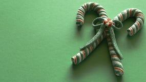 Zuckerstangen gebunden in einem Bogen auf festlichem grünem Hintergrund lizenzfreies stockfoto