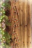 Zuckerstangen und Weihnachtsbaumaste auf natürlichem Holztisch im Hintergrund lizenzfreies stockbild