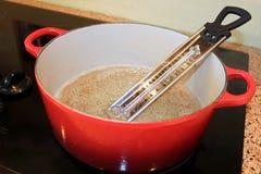 Zuckerthermometer im Topf kochendem Zucker Stockfotos