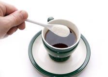 Zuckerzusatz in einem Cup mit Tee Lizenzfreie Stockfotos