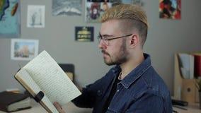 Zufälliger reifer hispter Mannstudent mit dem gelben Haar des stilvollen Haarschnitts, das zu Hause Büro ein großes braunes Buch  stock video footage