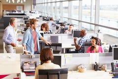 Zufällig gekleidete Kollegen, die in einem Bürogroßraum sprechen stockbilder