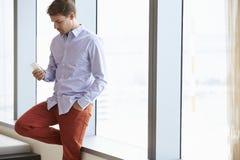 Zufällig gekleideter Geschäftsmann Using Mobile Phone im Büro Stockfoto
