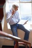 Zufällig gekleideter Geschäftsmann Working On Stairs bei der Büro-Unterhaltung Stockbilder