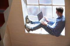 Zufällig gekleideter Geschäftsmann Working On Stairs im Büro Stockbild
