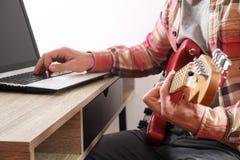 Zufällig gekleideter junger Mann des Bartes mit der Gitarre, die zu Hause Lieder im Raum spielt Laptop auf Tabelle On-line-Gitarr stockfotografie