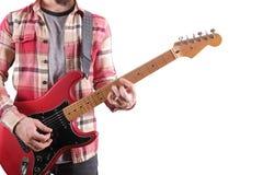 Zufällig gekleideter junger Mann mit der Gitarre, die Lieder lokalisiert auf Weiß spielt Laptop auf Tabelle On-line-Gitarrenlekti stockbilder