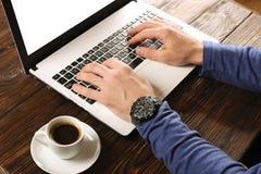 Zufällig gekleideter Student/Blogger/Verfasser/Mann, der an PC-Laptop, schreibend auf Tastatur arbeitet und schreiben den Blogart Stockfoto