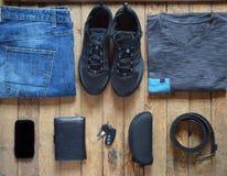 Zufällige Ausstattungen der Männer Mannschuhe, -kleidung und -Zubehör auf hölzernem Hintergrund - graues T-Shirt, Blue Jeans, Tur stockfotografie
