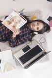 Zufällige Bloggerfrau, die eine Zeitschrift in ihrem Modebüro liest. stockfotos