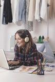 Zufällige Bloggerfrau, die mit Laptop in ihrem Modebüro arbeitet. stockfotos