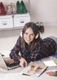 Zufällige Bloggerfrau, die mit Laptop und Zeitschrift in ihrem Modebüro arbeitet. stockfotografie