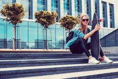 Zufällige blonde Frau in der Sonnenbrille und im Denimhemd Stockfoto