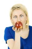 Zufällige blonde Frau, die einen Apfel isst Stockbilder