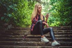 Zufällige blonde Frau mit longboard unter Verwendung des Smartphone Lizenzfreies Stockbild