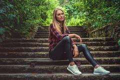 Zufällige blonde weibliche Aufstellung mit longboard auf Treppe Stockbilder