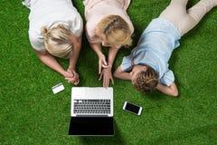 Zufällige Familie unter Verwendung des Laptops mit Kreditkarte beim Lügen auf dem Gras Stockfoto