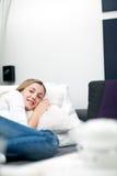 Zufällige faule junge Frau, die auf einem Bett schläft Stockfotografie