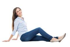 Zufällige Frau, die über weißem Hintergrund sitzt Stockfotos